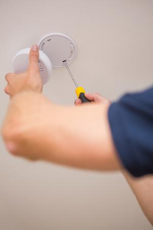 smoke alarm: Handyman installing smoke detector with screwdriver on the ceiling Stock Photo