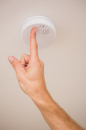 one hand: Handyman installing a smoke detector on the ceiling