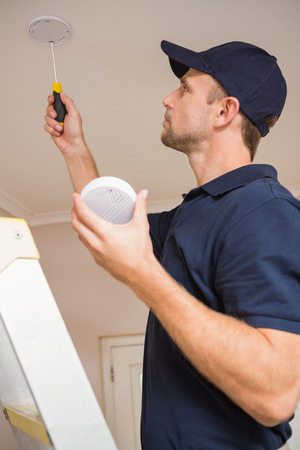 detector: Handyman installing smoke detector with screwdriver on the ceiling Stock Photo