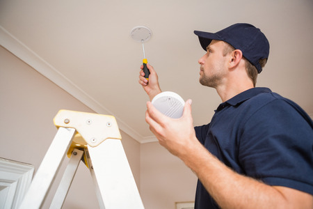 Handyman installing smoke detector with screwdriver on the ceiling Stockfoto