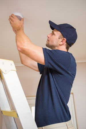 smoke: Focused handyman installing smoke detector with screwdriver on the ceiling