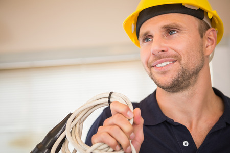 building contractor: Construction worker posing with cables in a new house Stock Photo