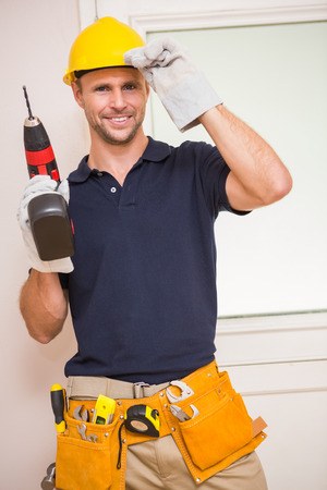 power tool: Construction worker posing while holding power tool in a new house Stock Photo