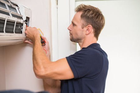 cold air: Focused handyman testing air conditioning on the wall