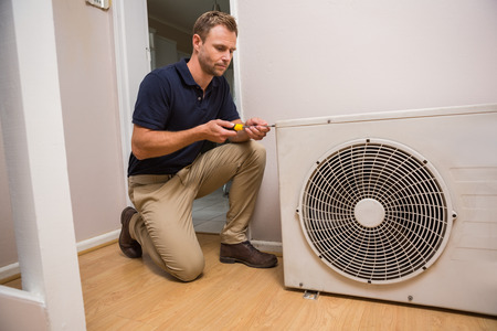 refrigeration: Focused handyman fixing air conditioning in a new house