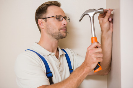 Handyman hammering nail in wall in a new house