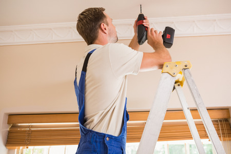 handyman tools: Handyman using a cordless drill to the ceiling in a new house