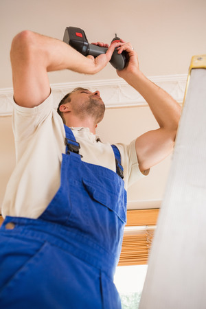 Handyman using a cordless drill to the ceiling in a new house photo