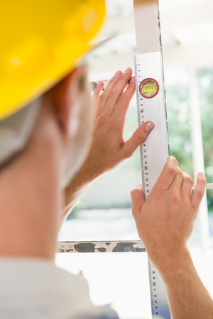 spirit level: Construction worker using spirit level in a new house
