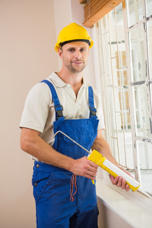 Man putting filling between window and wall in a new house photo