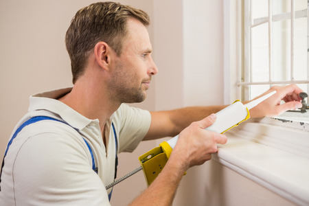 window repair: Man putting filling between window and wall in a new house Stock Photo