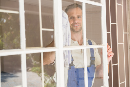 window cleaner: Handyman cleaning the window and smiling in a new house Stock Photo