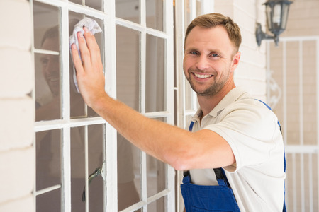 Handyman cleaning the window and smiling in a new house Stockfoto