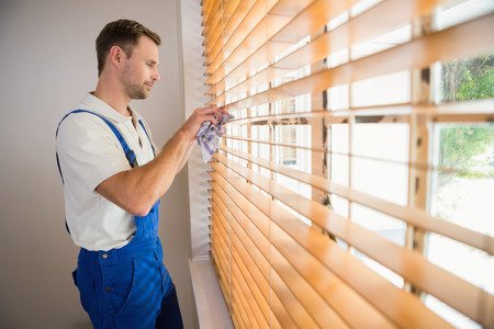 Handyman cleaning blinds with a towel in a new house Foto de archivo