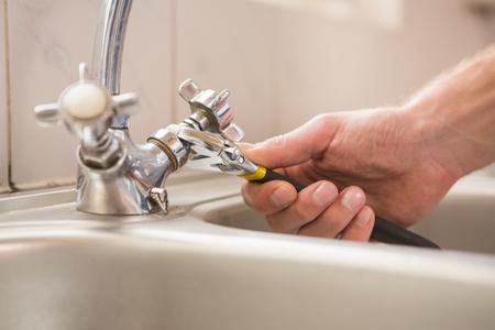fontanero: Hombre que fija grifo con pinzas en casa en la cocina