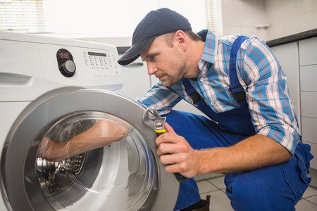 fixing: Handyman fixing a washing machine in the kitchen