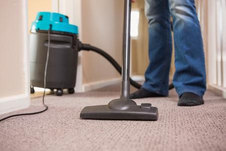 clean carpet: Close up a young man vacuuming at home Stock Photo