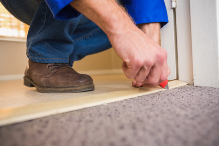 Carpet floor: Handyman laying down a carpet in a new house