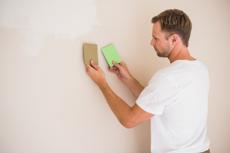 sanding block: Handsome decorator sanding down the wall  in a new home