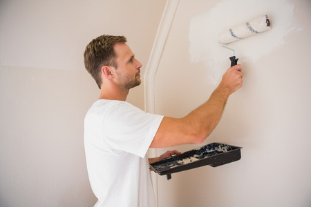 painting house: Painter painting the walls white in a new house Stock Photo