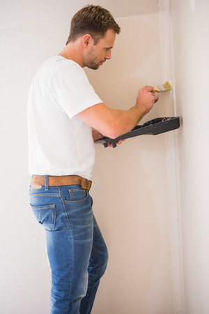 Painter painting the walls white in a new house photo