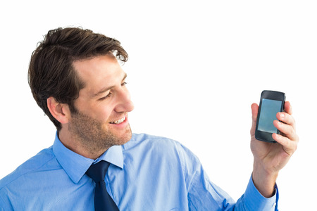 Smiling businessman showing smartphone to camera on white background photo