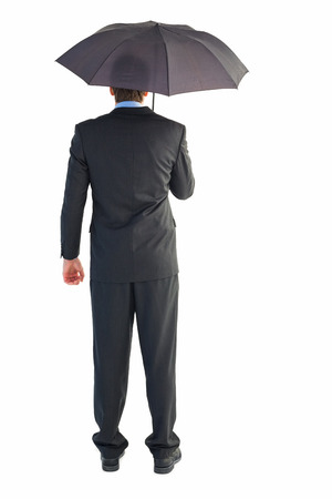 sheltering: Rear view of businessman sheltering with umbrella on white background Stock Photo