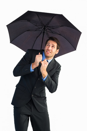 sheltering: Businessman sheltering with black umbrella on white background Stock Photo