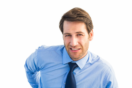 Handsome businessman with back pain standing on white background