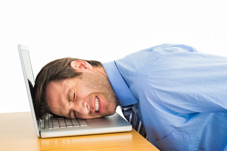 over worked: Businessman resting head on keyboard in office