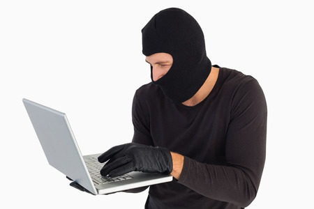 thievery: Focused burglar standing holding laptop on white background Stock Photo