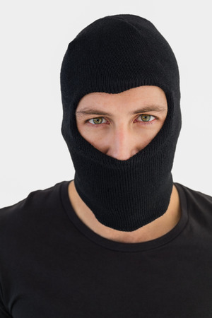 thievery: Portrait of burglar wearing a balaclava on white background Stock Photo