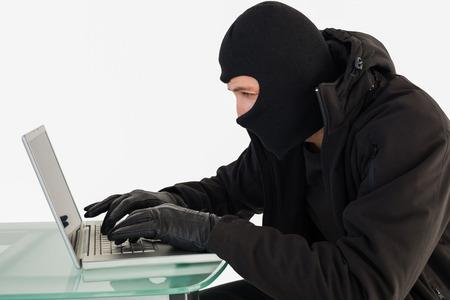 intruding: Robber sitting at desk hacking a laptop on white background