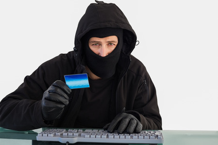 thievery: Burglar shopping online with laptop while looking at camera on white background Stock Photo