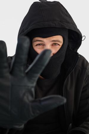 intruding: Portrait of burglar wearing a balaclava on white background Stock Photo
