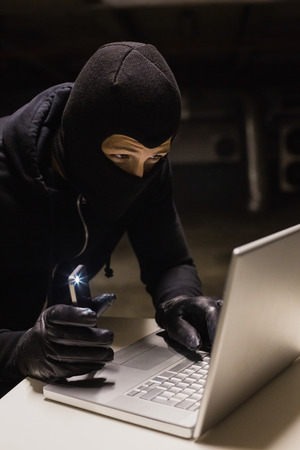thievery: Robber hacking a laptop while making light with his phone on black background