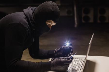 intruding: Robber shopping online while making light with his phone on black background Stock Photo