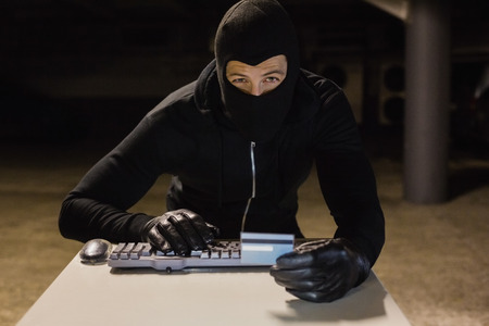 intruding: Burglar shopping online with laptop on black background
