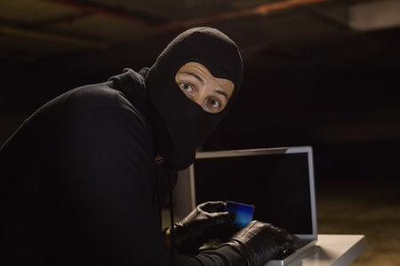 intruding: Burglar shopping online with laptop while looking at camera on black background