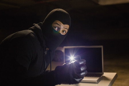 intruding: Robber looking at camera while making light with his phone on black background Stock Photo