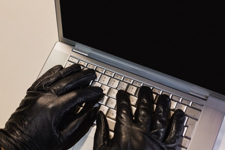 thievery: Close up of burglar hacking a laptop on black background