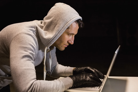 thievery: Man in hood jacket hacking a laptop on black background