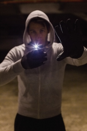 intruding: Man in hood jacket standing while making light with his phone on black background Stock Photo