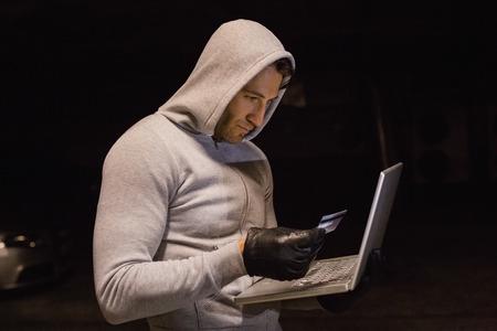 intruding: Man in hood jacket standing shopping online on black background