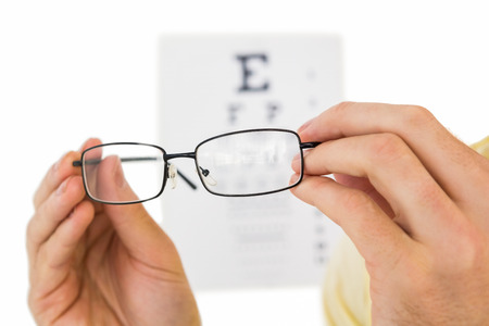 sight chart: Glasses held up to read eye test on white background
