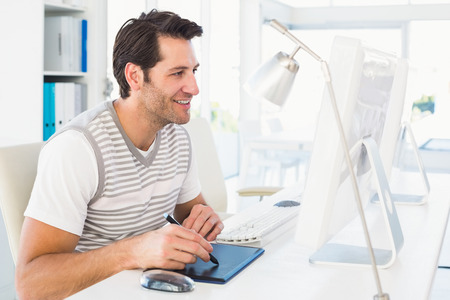 digitizer: Casual man working at desk with computer and digitizer in his office