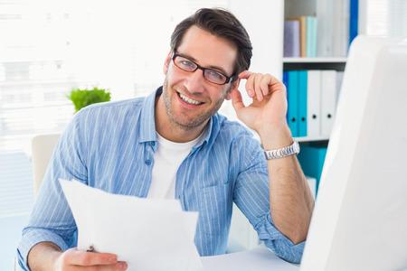 Sorrindo editor de fotos no trabalho que prende a folha de contato no escritório