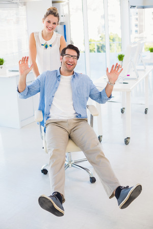 Man on swivel chair with hands up in office photo
