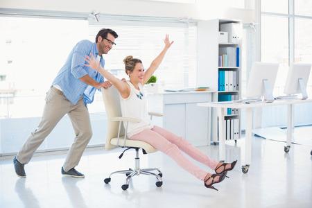 사무실의 회전 의자에 재미있는 사진 편집자 미소 짓기