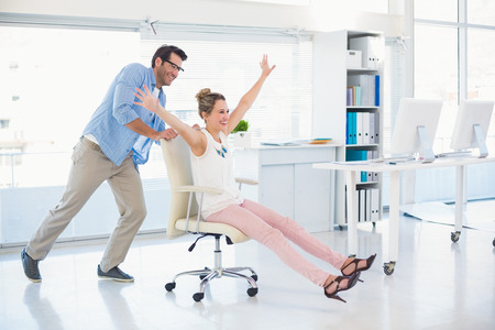 sillon: Sonre�r editores de fotograf�a que se divierten con en una silla giratoria de oficina Foto de archivo